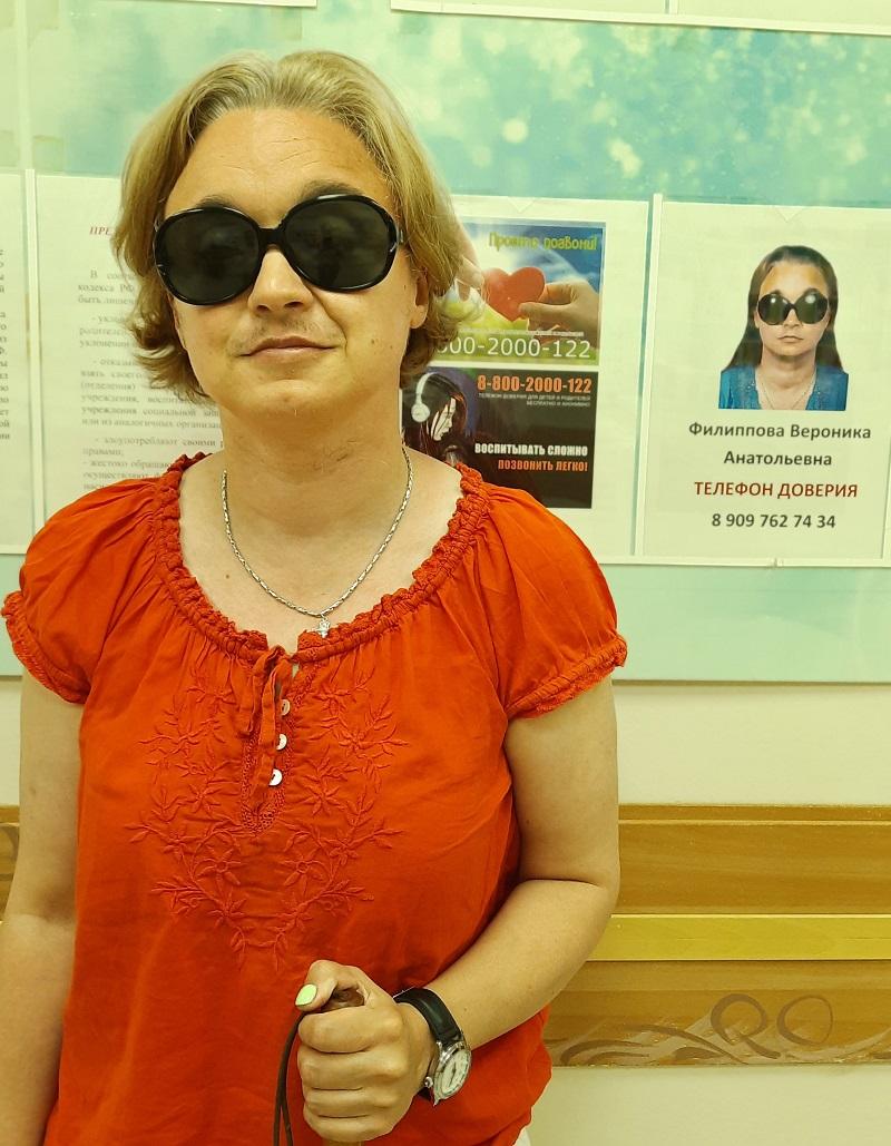 Фото Вероника Филиппова на фоне стенда в школе для слепых и слабовидящих г. Кисловодска, на котором отображено её фото и указано, что Вероника является специалистом телефона доверия